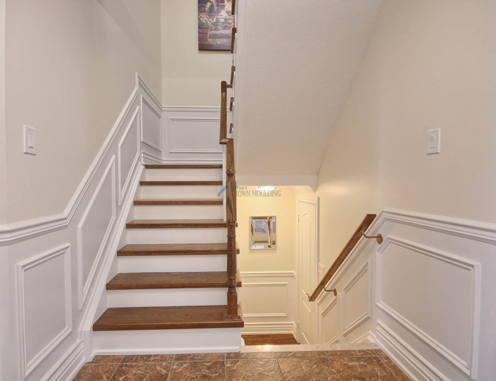 wood stairs with trimwork and wainscoting