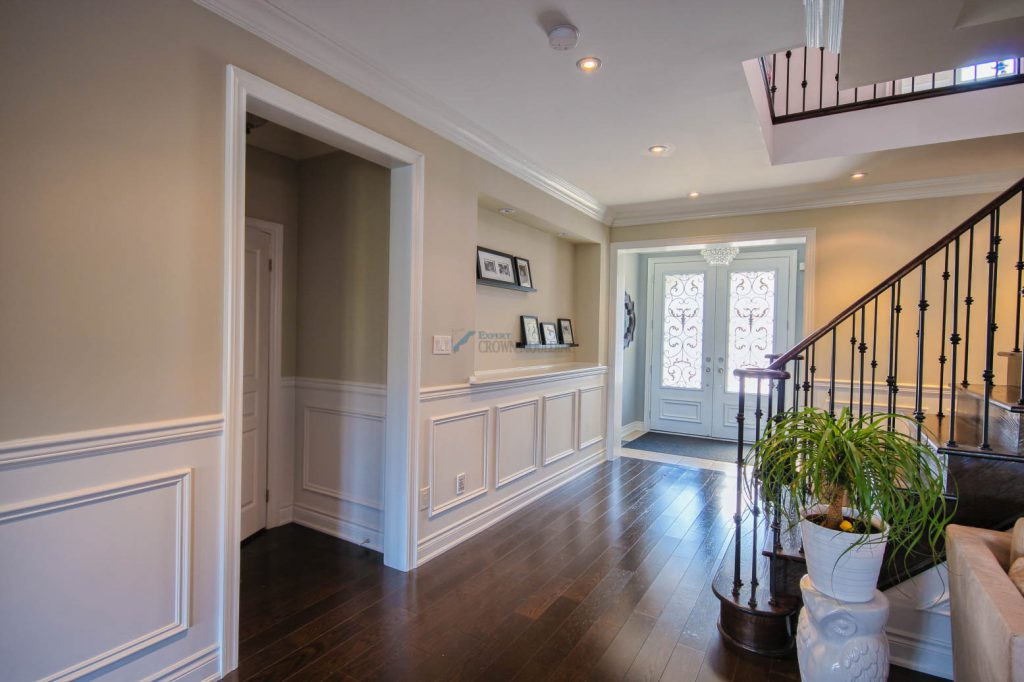 halllway with wall shelf unit and crown mouldings