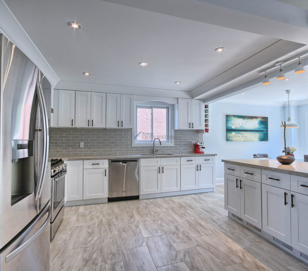 kitchen cabinets and ceiling with crown moulding and pot lights